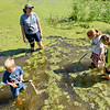 BEN MIKESELL | THE GOSHEN NEWS<br /> Naturalist Krista Daniels, top, laughs with Nature Explorer Day Campers as they wade through the water looking for bugs to scoop up with their nets Wednesday at Ox Bow Park.