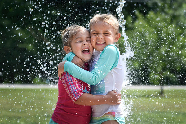BEN MIKESELL | THE GOSHEN NEWS<br /> Maci Bacigal, 3, left, hugs her sister Peyton, 5, both of Goshen, as they stand underneath the water bucket Friday afternoon at the Rieth Park splash pad in Goshen.