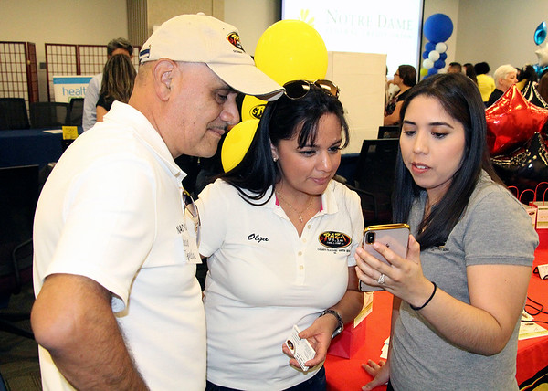 "AIMEE AMBROSE | THE GOSHEN NEWS <br /> (from left) ""Nacho"" Zepeda, Olga Zepeda and Jennifer De Luna of La Raza radio station in Goshen review a video they took during the Indiana Latino Business Expo 2019 at the Ivy Tech Community College campus along C.R. 18 near Elkhart Wednesday."
