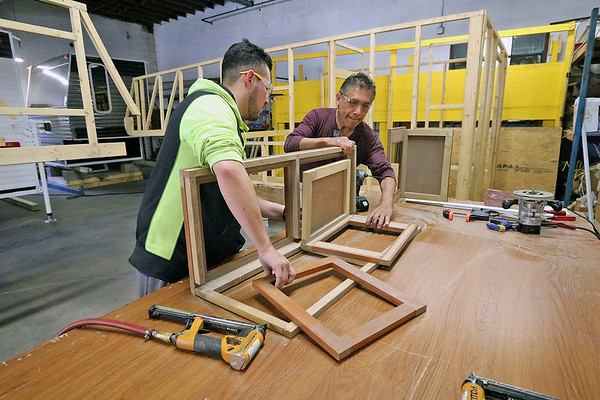 Roger Schneider | The Goshen News<br /> Jonathan Leal, left, and Cesar Hernandez, assemble a cabinet for a truck camper at Journey RV in Goshen. The new manufacturer is part of a growing local economy that has been cited by the Walton Foundation as having one of the best growth rates in the nation.