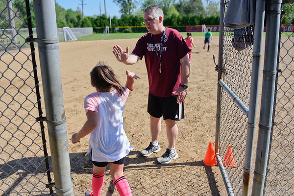 BEN MIKESELL | THE GOSHEN NEWS<br /> Coach Mark Aukerman high-fives with Aubrey Morales, 6, as she runs onto the field for soccer camp Tuesday morning at Shanklin Park.