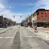 ROGER SCHNEIDER | The Goshen News<br /> In this April 22 file photo, a skateboarder and pedestrians begin to cross Main Street in downtown Goshen at Washington Street. City officials had just announced that three Main Street intersection signals were to blink red as an experiment in changes planned for Main Street.