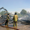 AIMEE AMBROSE | THE GOSHEN NEWS <br /> Firefighters spray a hot spot while an excavator clears debris where a fire destroyed a barn at the Miller Excavating property along U.S. 20 in Shipshewana Friday.