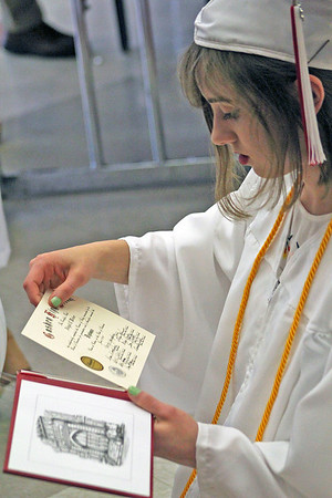 Roger Schneider | The Goshen News<br /> Abigail Weber places her certificate of graduation into her diploma folder following the Goshen High School graduation Sunday.
