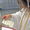 Roger Schneider | The Goshen News<br /> Abigail Weber places her certificate of graduation into her diploma folder following the Goshen High School graduation Sunday.