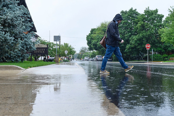 BEN MIKESELL | THE GOSHEN NEWS<br /> A man walks across Fifth Street during the afternoon rainfall Thursday in Goshen.