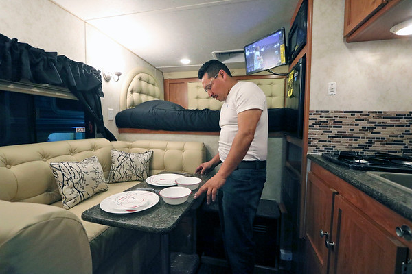 ROGER SCHNEIDER | The Goshen News<br /> Jose Francisco Leal, whose family has created the new recreational vehicle company, Journey RV, adjusts a table setting inside one of the company's pickup truck campers. The company has joined the growing manufacturing base in the Elkhart-Goshen Metropolitan Statistical Area, whiich has been cited by the Walton Foundation as being on the nation's most dynamic MSAs.