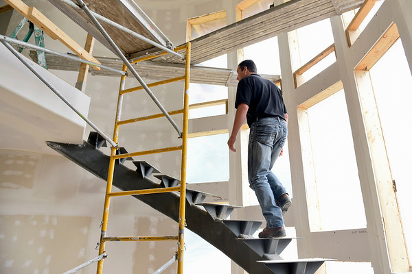BEN MIKESELL | THE GOSHEN NEWS<br /> Titus Troyer, general manager of Miller Brothers Builders, walks up the spiral staircase in one of this year's hard hat homes Wednesday afternoon for the Elkhart Parade of Homes beginning this weekend.