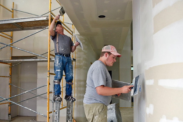 BEN MIKESELL | THE GOSHEN NEWS<br /> Miller Brothers Builders workers Scott Johnson, left, and his son Isaac work on the house being built at 26301 C.R. 52, which will be featured in this year's Elkhart Parade of Homes beginning this weekend.