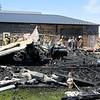 AIMEE AMBROSE | THE GOSHEN NEWS <br /> Debris covers the scene where a fire destroyed a barn and a few vehicles and damaged a couple other buildings at Miller Excavating along U.S. 20 in Shipshewana Friday.