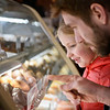 BEN MIKESELL | THE GOSHEN NEWS<br /> Tristan Beechy-King, of Goshen, explains to his daughter Emery, 6, how to pronounce paczki, which were on display Tuesday afternoon at Dutch Maid Bakery. The bakery staff made around 7,000 paczki for Fat Tuesday, and the line to purchase them Tuesday morning was out the door, manager Andrew Bird said.