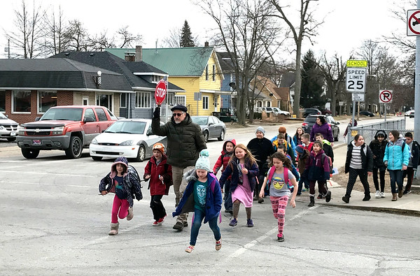 JOHN KLINE | THE GOSHEN NEWS<br /> Leon Bauman, school counselor for Chandler Elementary School, leads a group of students across Madison Street at the Eighth Street intersection as school lets out Thursday afternoon.