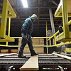 BEN MIKESELL | THE GOSHEN NEWS<br /> Wible Lumber worker Colton Yant inspects planks as they roll across the sorting line Wednesday afternoon at the lumber mill in South Milford.