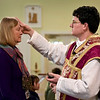 BEN MIKESELL | THE GOSHEN NEWS<br /> Pastor Royce Gregerson, right, places ashes on teacher Diane Kreager's head during Ash Wednesday mass at St. John the Evangelist Catholic Church.
