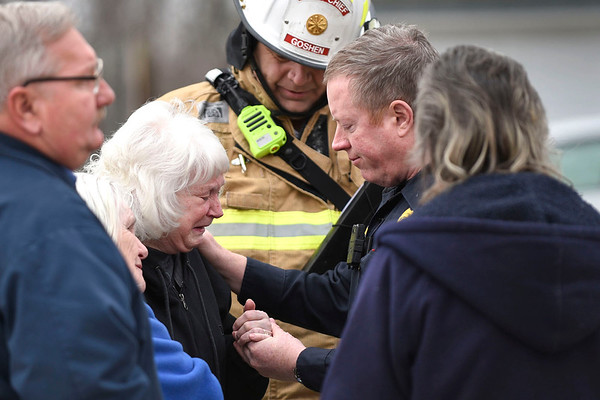 BEN MIKESELL | THE GOSHEN NEWS<br /> Goshen police officer Jeff Schrock, right, consoles Diann Grise after her husband Charles died in a house fire Thursday afternoon at 425 N First St. in Goshen.