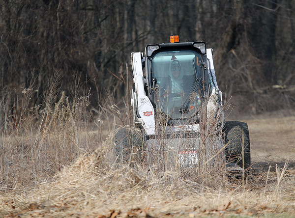 Roger Schneider | The Goshen News<br /> Cameron Hideman drives a heavy-duty moer through dried prairie plants at Shanklin Park in Goshen.The department's parks feature several small prairies, which provide food and shelter each summer for insects, birds and animals.