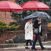 BEN MIKESELL | THE GOSHEN NEWS<br /> Sandy Amt, Elkhart, right, looks as she crosses Washington Street with Joan Clark, Elkhart, while walking down Main Street Wednesday afternoon in Goshen. A cold rain prompted the women to use their umbrellas. The National Weather Service forecasts that the chance for rain will diminish to 20 percent today and by Saturday the weather will have cleared and it will be sunny and cool.