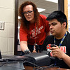 BEN MIKESELL | THE GOSHEN NEWS<br /> Goshen High School engineering teacher Jen Yoder, left, helps junior Carlos Urenda use the new flight simulator during class Wednesday morning at GHS.