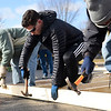 BEN MIKESELL | THE GOSHEN NEWS<br /> Bethany Christian sophomore Aaron Yeakey, center, hammers a nail into a panel while building a home Saturday morning with Habitat for Humanity in the Bethany Christian Schools parking lot.