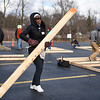 BEN MIKESELL | THE GOSHEN NEWS<br /> Bethany Christian assistant Asenath Odondi, on an exchange program from Kenya, helps carry planks of wood Saturday morning while building a Habitat for Humanity in the Bethany Christian Schools parking lot.