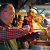 GEOFF LESAR | THE GOSHEN NEWS<br /> <br /> Goshen Clay Artists Guild member Ben Grove, Elkhart, pours chili from a ladle into a ceramic bowl Saturday evening during the 19th annual Empty Bowl Soup Supper at the Goshen Farmers Market. More than 500 people attended the event, which raises funds for Goshen Interfaith Hospitality Network.