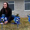 BEN MIKESELL | THE GOSHEN NEWS<br /> CASA supervisor Lauren Kelley smiles as she places a pinwheel in the ground Thursday afternoon outside of Child & Parent Services (CAPS) in Elkhart. Nearly 750 pinwheels were planted outside the building on Hively Avenue, and CAPS will distribute about 5000 throughout April to honor National Child Abuse Prevention Month.