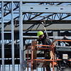 BEN MIKESELL | THE GOSHEN NEWS<br /> Derek Haywood, Middlebury, with CDR Construction works on the steel framework for The O Wednesday in Linway Plaza. Construction on the building is expected to be finished around September, Heather Tobias Harren, one of the investors of The O said.