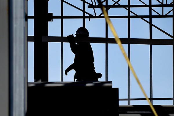 BEN MIKESELL | THE GOSHEN NEWS<br /> A CDR Construction worker carries a steel beam Wednesday morning while constructing the framework for The O in Linway Plaza. Construction on the building is expected to be finished around September, Heather Tobias Harren, one of the investors of The O said.