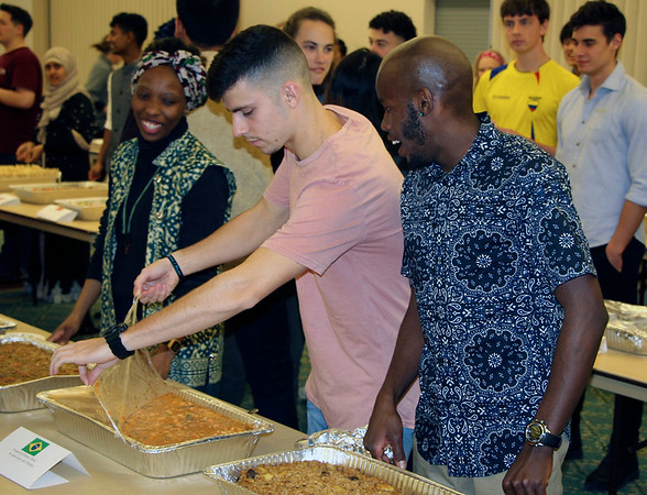 JOHN KLINE | THE GOSHEN NEWS<br /> Goshen College International Student Club members, from left, Neo Tau, of South Africa, Gabriel Costa, of Brazil, and Vincent Kibunja, of Kenya, prepare various international dishes for serving during the kickoff of the annual ISC Coffeehouse event at the college Saturday evening.