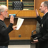 JOHN KLINE | THE GOSHEN NEWS<br /> Michael Landis, member of the Goshen Board of Public Works and Safety, left, conducts the swearing-in ceremony for Lucas L. Mason following his promotion to the rank of EMS sergeant with the Goshen Fire Department during the board's meeting Monday afternoon.