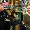 """BEN MIKESELL   THE GOSHEN NEWS<br /> Yogi, a German shepherd K-9 unit, licks Shipshewana police officer Nick Byroad, left, while accompanied by Jennifer Lipscomb, right, Monday morning inside Davis Mercantile in Shipshewana. Lipscomb, the owner of Simple Sounds, bought newly graduated K-9 a bulletproof vest so he can be as protected as officer Byroad. """"I'm so thankful for everything they do,"""" Lipscomb said, """"and our fuzziest members need to be protected too."""""""
