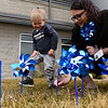 BEN MIKESELL | THE GOSHEN NEWS<br /> Cohen Kelley, 2, plants pinwheels with Helen Calvin, director of CASA, Thursday afternoon outside of Child & Parent Services (CAPS) in Elkhart. Nearly 750 pinwheels were planted outside the building on Hively Avenue, and CAPS will distribute about 5000 throughout April to honor National Child Abuse Prevention Month.