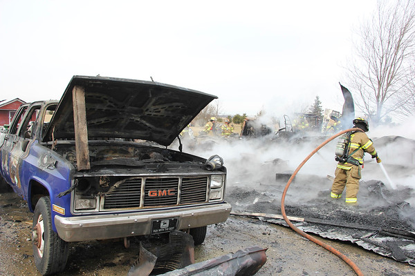 AIMEE AMBROSE | THE GOSHEN NEWS Ligonier firefighters extinguish the remaining flames of a fire that destroyed a structure and vehicles inside at a home, 11485 C.R. N. 1025 West, near Ligonier Monday. A barn was also damaged as well as a pickup truck parked outside.