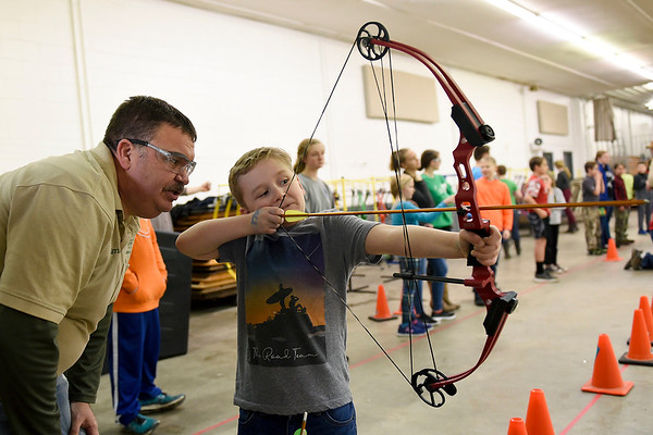 BEN MIKESELL | THE GOSHEN NEWS<br /> Elkhart County 4-H Shooting Sports Instructor Tim Wietstock, left, helps Peyton Woods, 8, of Middlebury, draw his bow during the last indoor shoot of the season Thursday evening at the Elkhart County 4-H Fairgrounds. The next open shooting event for the club will be outdoors April 6.