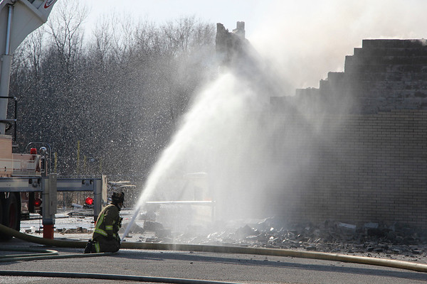 AIMEE AMBROSE | THE GOSHEN NEWS <br /> An Elkhart firefighter sprays water as part of the department's response to extinguish a fire at Forest River RV plant 59 Tuesday. The fire destroyed the facility along C.R. 15.