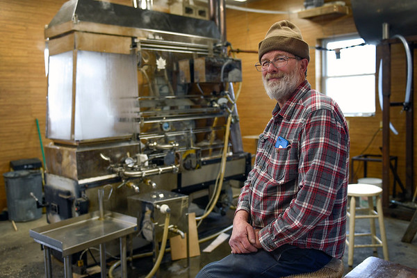 BEN MIKESELL | THE GOSHEN NEWS<br /> Mark Matthews sits next to his evaporator while making a batch of maple syrup Wednesday evening in his sugar shack in Bristol.