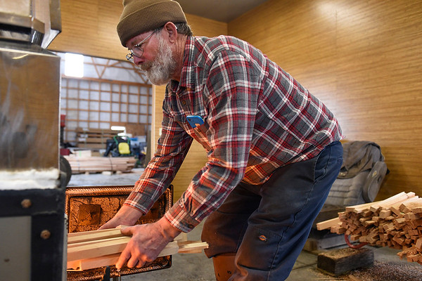 BEN MIKESELL | THE GOSHEN NEWS<br /> Mark Matthews, Bristol, adds wood to the fire under his evaporator while making maple syrup in his sugar shack Wednesday evening at his home.