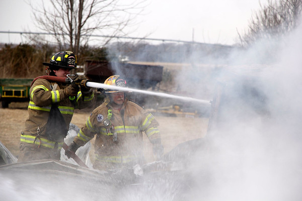 AIMEE AMBROSE | THE GOSHEN NEWS Ligonier firefighters extinguish the remaining flames of a fire that destroyed a structure and vehicles inside at a home, 11485 C.R. N. 1025 West, near Ligonier Monday. A barn was also damaged.