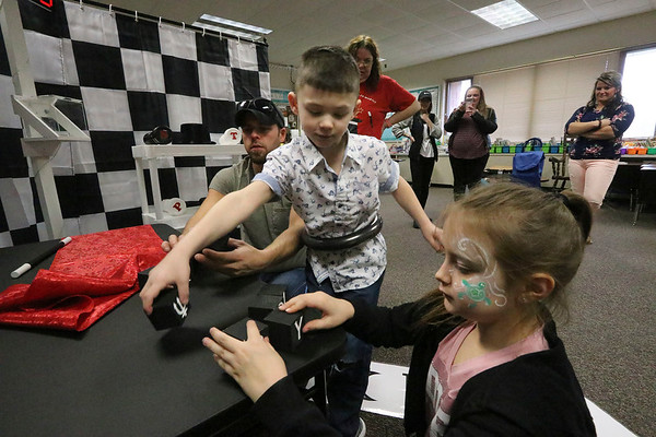 "AIMEE AMBROSE | THE GOSHEN NEWS <br /> Jaxon Young, 7, and his cousin, Marissa Ritz, 10, solve a puzzle with Jaxon's dad, Zachary Young, New Paris, in an escape room challenge during the annual Oxbowzaar at Oxbow Elementary School, 23525 C.R. 45, Saturday. ""I did it,"" Jaxon exclaimed after unlocking a box during the challenge provided by Escape Down Under in Goshen."