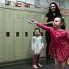AIMEE AMBROSE | THE GOSHEN NEWS Ellie Burton tries her luck at the Frisbee Toss while her sister Emma Burton (left) and mother Jessica Burton (right) watch during Saturday's annual Oxbowzaar at Ox Bow Elementary School, 23525 C.R. 45. The three from Indianapolis visited the school where the girls' grandmother, Jodi Riester, is a third grade teacher.