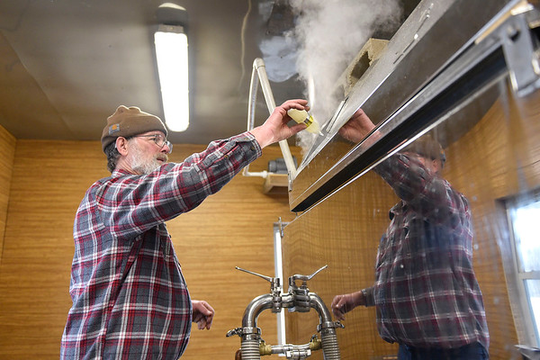 BEN MIKESELL | THE GOSHEN NEWS<br /> Mark Matthews, of Bristol, pours drops of a defoaming oil into his vat of sap while making maple syrup Wednesday afternoon on his property on C.R. 131. Matthews, a retired electrician, has made syrup by tapping the red maple trees on his lot for 24 years, and this season will be his last.