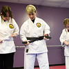 BEN MIKESELL | THE GOSHEN NEWS<br /> Instructor Darlene Guthrie, center, shows Diana Miller, left, Elkhart, and her daughter Megan, 11, how to tie their belts before class Tuesday evening at the Elkhart Okinawa Karate Club.