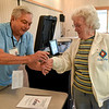 BEN MIKESELL | THE GOSHEN NEWS<br /> Facilitator Bob Schrameyer, left, stamps Goshen-resident Carol Manahan's hand after she casts her ballot in Tuesday's municipal election at the Salvation Army.