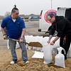 BEN MIKESELL | THE GOSHEN NEWS<br /> Brian Gill, store manager at Rent-A-Center, shovels sand into bags with employee Garrett Nisley at the corner of Chicago Avenue and Pike Street in Goshen.