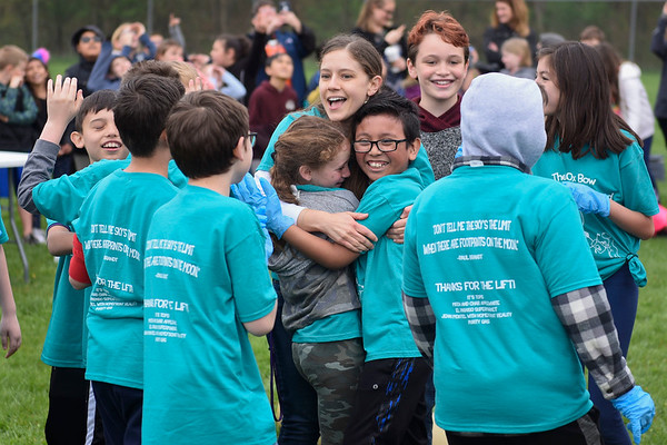 BEN MIKESELL | THE GOSHEN NEWS<br /> Fourth-graders Niya Franks and Jonathan Franco Guzman hug their teacher Elizabeth King, center, as they celebrate the successful launch of their weather balloon Friday morning at Ox Bow Elementary School. The students in the Ox Bow StratoSOARus Squad spent four months learning about weather patterns and layers of the atmosphere leading up to Friday's launch.