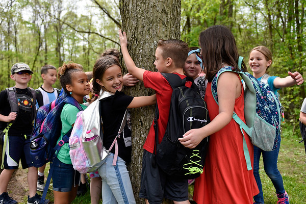 BEN MIKESELL | THE GOSHEN NEWS<br /> Benton Elementary second-grader Alexis Hochstetler, center, hugs a tree named Lincoln with her classmates in Tonya Beck's class Thursday morning at the Benton River Preserve County Park. The students visited the tree four times throughout the year, once during each season, to observe different patterns in nature and the environment.