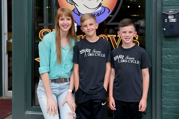 BEN MIKESELL | THE GOSHEN NEWS<br /> Kate Leaman, owner of Shirley's Gourmet Popcorn in Goshen, left, stands with Owen Holmes, 9, center, and his brother Tyler, 8, outside Shirley's Wednesday afternoon in Goshen.