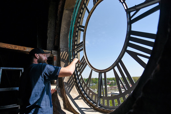 BEN MIKESELL | THE GOSHEN NEWS<br /> John Pelance, with Smith's Bell and Clock Service, puts primer on the clock frame Wednesday morning in the Elkhart County Courthouse clock tower.