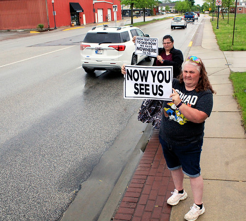 Roger Schneider | The Goshen News<br /> Mercede Gonzalez, in back, and her mother Donna Antomori, of Goshen, hold signs advocating for the city's homeless population, some of whom are facing a removal deadling for their camp along the mill race.