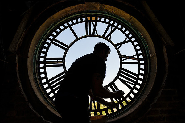BEN MIKESELL | THE GOSHEN NEWS<br /> Nic Clayton, with Smith's Bell and Clock Service, puts primer on the clock frame Wednesday morning in the Elkhart County Courthouse clock tower.
